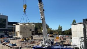 a crane lifts one standby generator into place near building 64